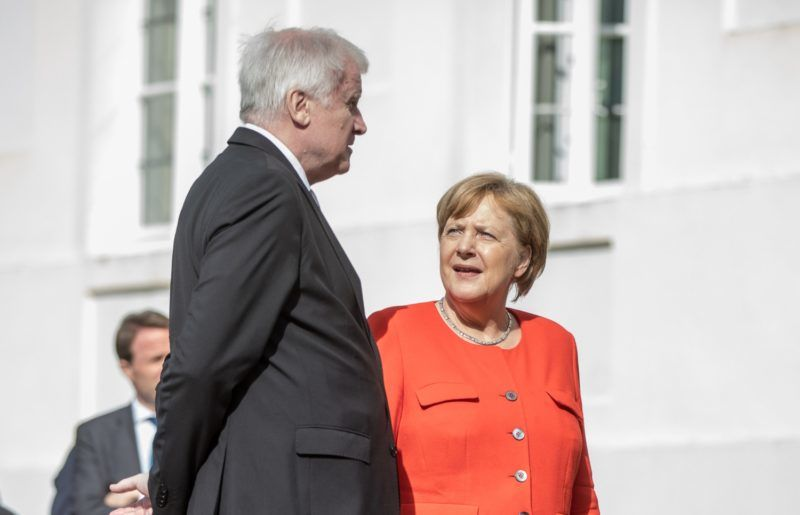 """German Interior Minister Horst Seehofer (L) talks with Chancellor Angela Merkel as they arrive for a family picture before a French-German ministerial conference to coordinate European reform proposals ahead of EU summit on June 28-29, 2018 on June 19, 2018, at the Meseberg Palace, northeastern Germany. German Chancellor Angela Merkel hosted French President Emmanuel Macron on June 19, 2018 to hammer out reforms that can stop the """"disintegration"""" of the European Union, torn by populist forces and deep discord over immigration. / AFP PHOTO / DPA / Michael Kappeler / Germany OUT"""