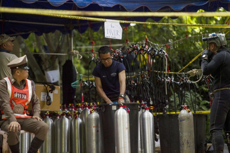 A Thai soldier prepare oxygen for a diver during rescue operations for 12 boys and their coach trapped in Tham Luang cave at near Tham Luang cave at the Khun Nam Nang Non Forest Park in the Mae Sai district of Chiang Rai province on July 4, 2018. A new video of a youth football team trapped in the bowels of a Thai cave emerged July 4 showing the boys laughing and saying they are well after their astonishing discovery by divers nine days after going missing. / AFP PHOTO / YE AUNG THU