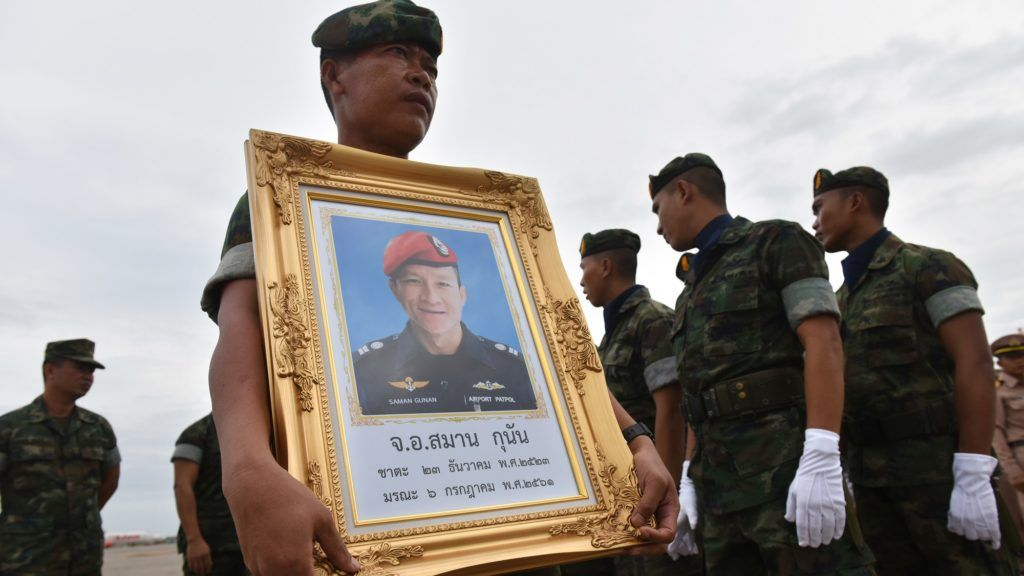 """A Royal Thai Navy soldier carries a portrait of Saman Gunan, a former navy SEAL who died in an accident in Tham Luang cave in a rescue mission for the trapped 12 boys and their coach during arrival honors for Gunan's remains at a military base in Chon Buri province  on July 6, 2018. A former Thai navy diver helping to rescue a football team trapped inside a flooded cave died July 6 as officials warned the window of opportunity to free the youngsters is """"limited"""".  / AFP PHOTO / THAI NEWS PIX / Panumas SANGUANWONG"""