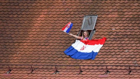 A woman waves a Croatian flag from the window of a house, during a welcome party for Croatian national football team, a day after their Russia 2018 World Cup final football match against France, near the Bana Jelacica Square in Zagreb, on July 16, 2018. Croatian media on July 16 hailed their team as heroes after the small country's historic success in reaching the World Cup final where France beat them 4-2. / AFP PHOTO / Andrej ISAKOVIC