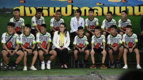 Twelve Thai boys and their football coach, rescued from a flooded cave after being trapped, attend a press conference in Chiang Rai on July 18, 2018, following their discharge from the hospital. The young footballers and their coach appeared healthy when they appeared before the media for the first time on July 18. / AFP PHOTO / LILLIAN SUWANRUMPHA