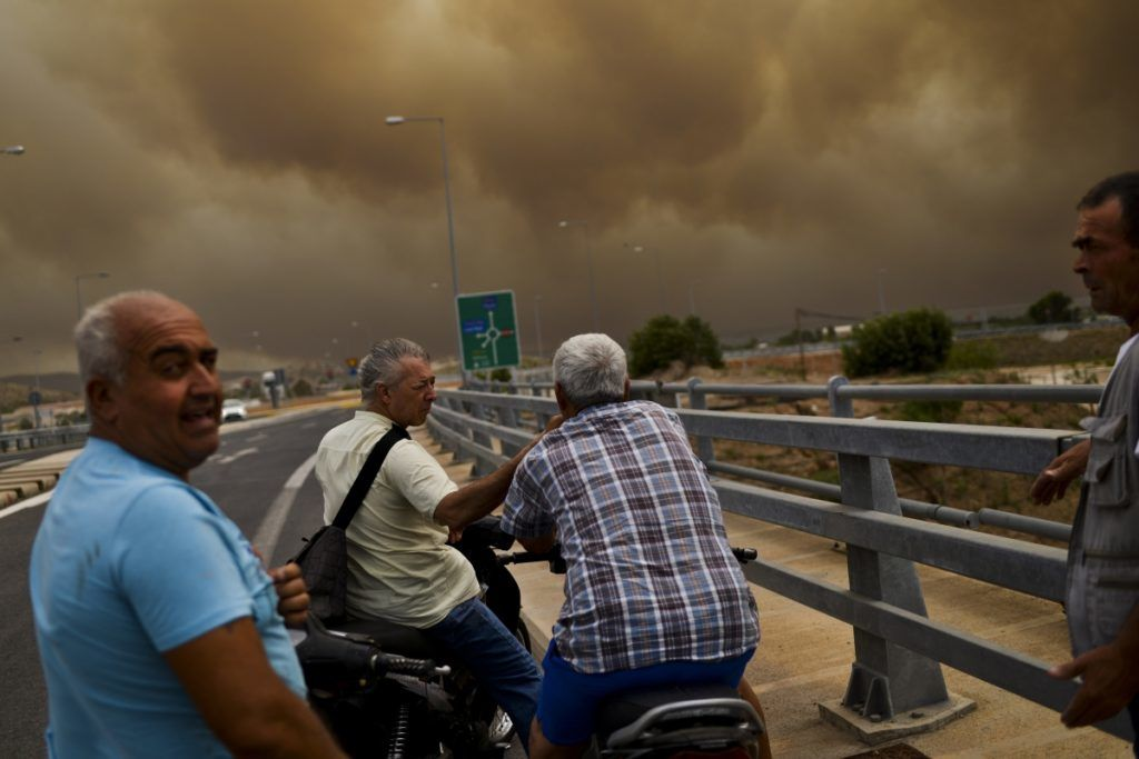 People look the smoke from a bridge as a wildfire burns in Kineta, near Athens, on July 23, 2018.  / AFP PHOTO / ANGELOS TZORTZINIS