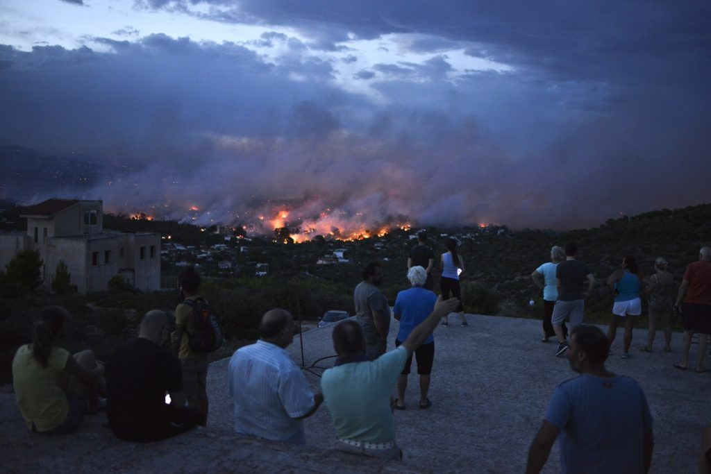 People watch a wildfire in the town of Rafina, near Athens, on July 23, 2018.  / AFP PHOTO / ANGELOS TZORTZINIS