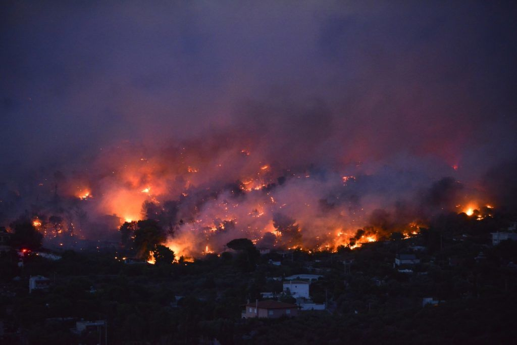 Flames rise as a wildfire burns in the town of Rafina, near Athens, on July 23, 2018.  / AFP PHOTO / ANGELOS TZORTZINIS