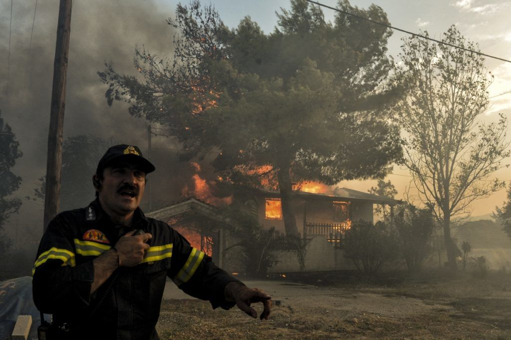"""A firefighter reacts as a house burns during a wildfire in Kineta, near Athens, on July 23, 2018. More than 300 firefighters, five aircraft and two helicopters have been mobilised to tackle the """"extremely difficult"""" situation due to strong gusts of wind, Athens fire chief Achille Tzouvaras said.   / AFP PHOTO / VALERIE GACHE"""