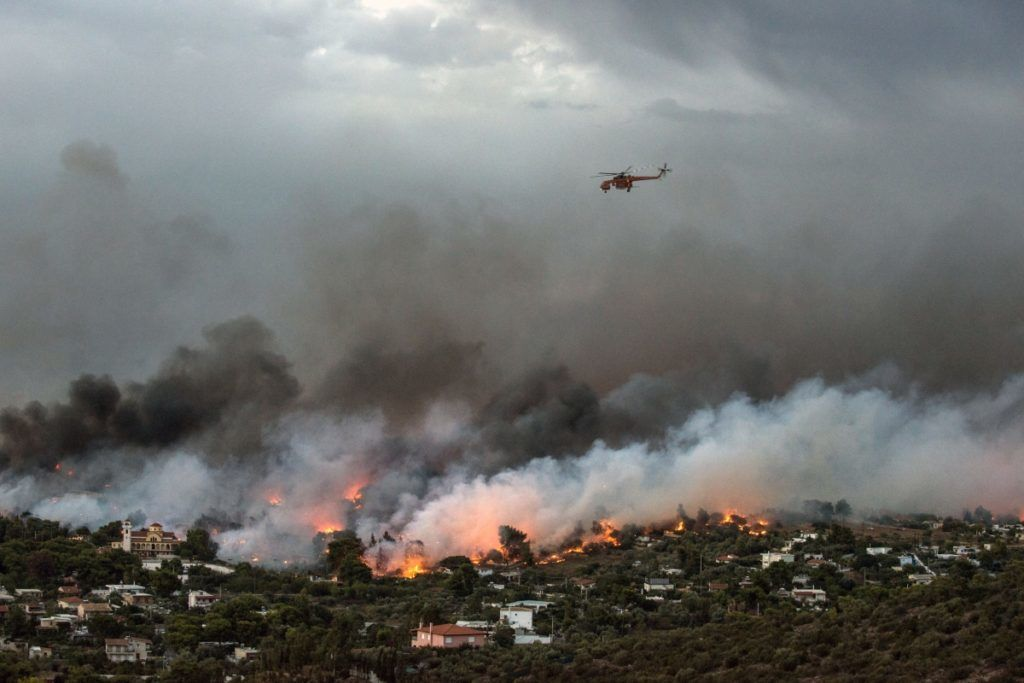 """A firefighting helicopter flies over a wildfire raging in the town of Rafina near Athens, on July 23, 2018.  At least five people have died and more than 20 have been injured as wild fires tore through woodland and villages around Athens on Monday, while blazes caused widespread damage in Sweden and other northern European nations. More than 300 firefighters, five aircraft and two helicopters have been mobilised to tackle the """"extremely difficult"""" situation due to strong gusts of wind, Athens fire chief Achille Tzouvaras said.   / AFP PHOTO / ANGELOS TZORTZINIS"""