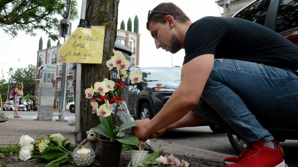 A man leaves flowers for the victims at the scene of last night shooting in Toronto, Ontario on July 23, 2018. Toronto police were seeking to determine a motive on after a 29-year-old man opened fire with a handgun on restaurant goers and pedestrians in a busy neighborhood of Canada's largest city overnight, killing two people and wounding 13. The suspect, who has not been identified, was found dead in a nearby alley after an exchange of gunfire with police.  / AFP PHOTO / Usman Khan