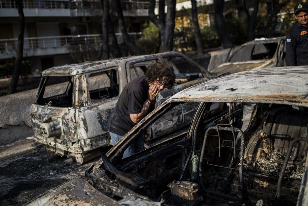 A woman tries to find her dog following a wildfire at the village of Mati, near Athens, on July 24, 2018. Fifty people have died and 170 have been injured in wildfires ravaging woodland and villages in the Athens region, as Greek authorities rush to evacuate residents and tourists stranded on beaches along the coast on July 24, 2018. The death toll soared with a Red Cross official reporting the discovery of 26 bodies in the courtyard of a villa at the seaside resort of Mati.  / AFP PHOTO / ANGELOS TZORTZINIS