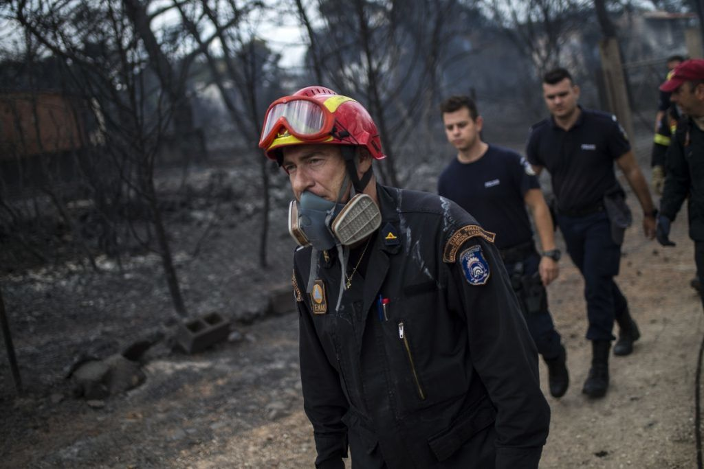Rescuers arrive at the area where dead bodies were found following a wildfire at the village of Mati, near Athens, on July 24, 2018. Fifty people have died and 170 have been injured in wildfires ravaging woodland and villages in the Athens region, as Greek authorities rush to evacuate residents and tourists stranded on beaches along the coast on July 24, 2018. The death toll soared with a Red Cross official reporting the discovery of 26 bodies in the courtyard of a villa at the seaside resort of Mati.  / AFP PHOTO / ANGELOS TZORTZINIS