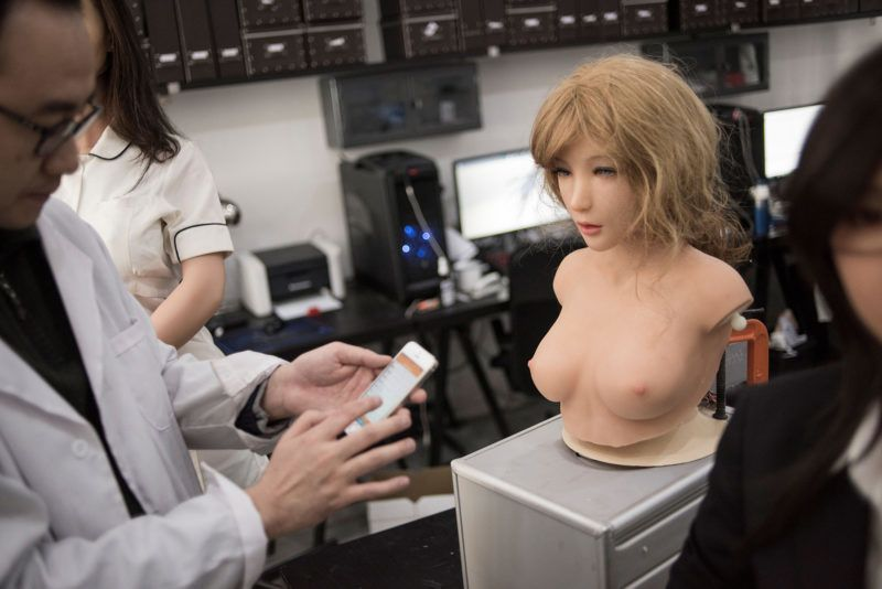 """This photo taken on February 1, 2018 shows an engineer displaying the facial expressions a robot can make, in a lab of a doll factory of EXDOLL, a firm based in the northeastern Chinese port city of Dalian.With China facing a massive gender gap and a greying population, a company wants to hook up lonely men and retirees with a new kind of companion: """"Smart"""" sex dolls that can talk, play music and turn on dishwashers. / AFP PHOTO / FRED DUFOUR / TO GO WITH China-sex-lifestyle, FOCUS by Joanna CHIU"""