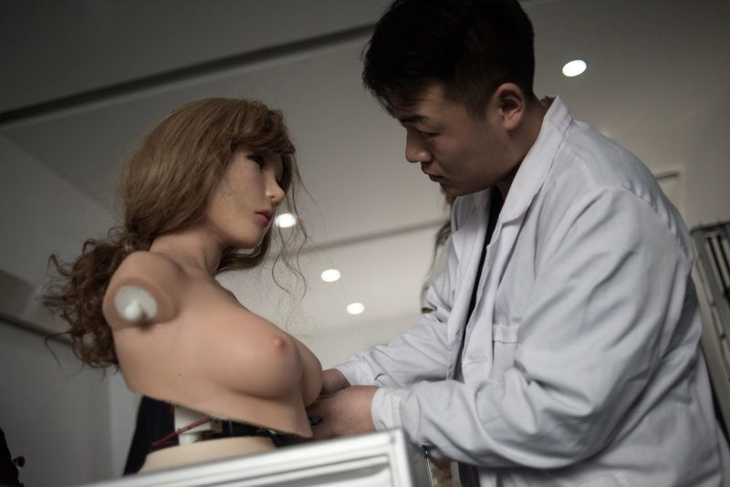 """This photo taken on February 1, 2018 shows an engineer making some electronic corrections to a robot at a lab of a doll factory of EXDOLL, a firm based in the northeastern Chinese port city of Dalian.With China facing a massive gender gap and a greying population, a company wants to hook up lonely men and retirees with a new kind of companion: """"Smart"""" sex dolls that can talk, play music and turn on dishwashers. / AFP PHOTO / FRED DUFOUR / TO GO WITH China-sex-lifestyle, FOCUS by Joanna CHIU"""