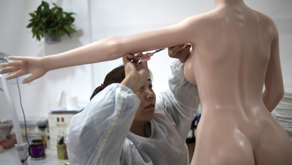 """This photo taken on February 1, 2018 shows a worker trimming the skin imperfections of a silicone doll at a factory of EXDOLL, a firm based in the northeastern Chinese port city of Dalian.With China facing a massive gender gap and a greying population, a company wants to hook up lonely men and retirees with a new kind of companion: """"Smart"""" sex dolls that can talk, play music and turn on dishwashers. / AFP PHOTO / FRED DUFOUR / TO GO WITH China-sex-lifestyle, FOCUS by Joanna CHIU"""
