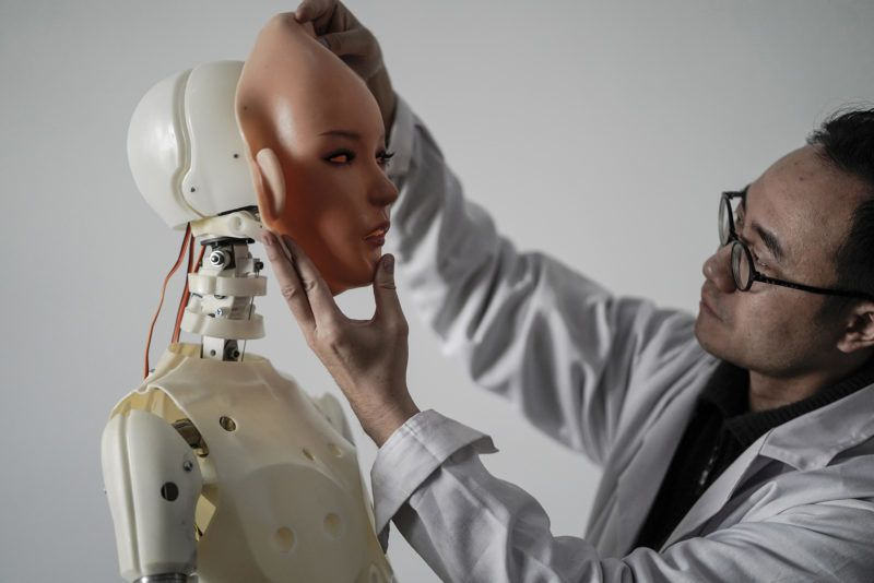 """This photo taken on February 1, 2018 shows an engineer holding a silicon face against the head of a robot at a lab of a doll factory of EXDOLL, a firm based in the northeastern Chinese port city of Dalian.With China facing a massive gender gap and a greying population, a company wants to hook up lonely men and retirees with a new kind of companion: """"Smart"""" sex dolls that can talk, play music and turn on dishwashers. / AFP PHOTO / FRED DUFOUR / TO GO WITH China-sex-lifestyle, FOCUS by Joanna CHIU"""
