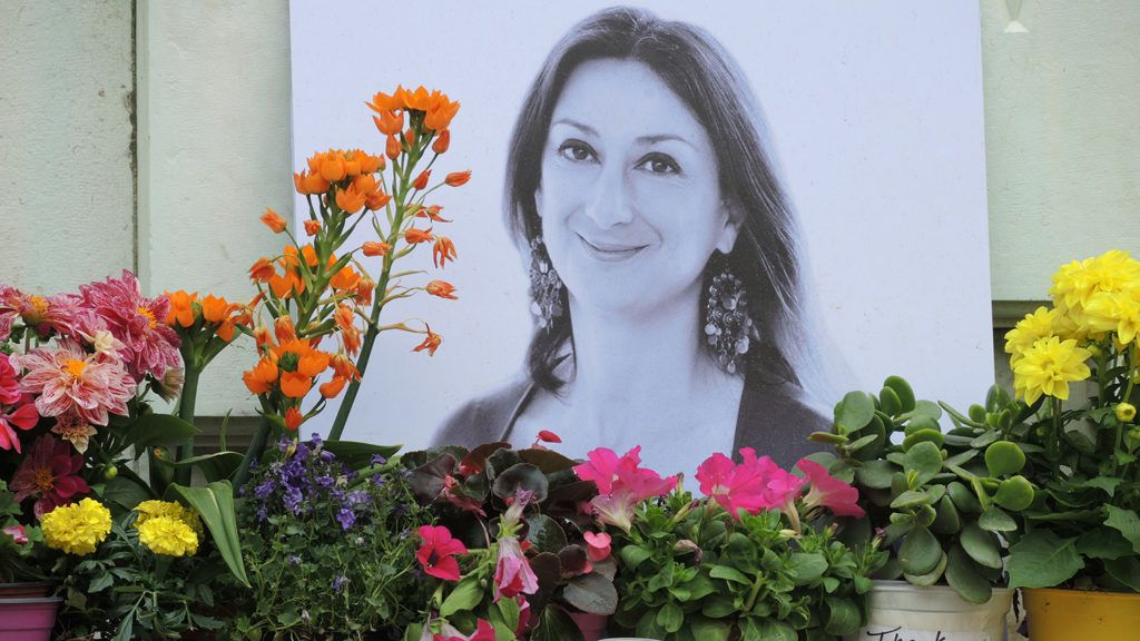 10 April 2018, Malta, Bidnija: At the feet of a memorial oposite the palace of justice are flowers and a photo in menory of the murdered journalist Daphne Caruana Galizia. Reasons for the attack are still unclear half a year after the event. Photo: Lena Klimkeit/dpa