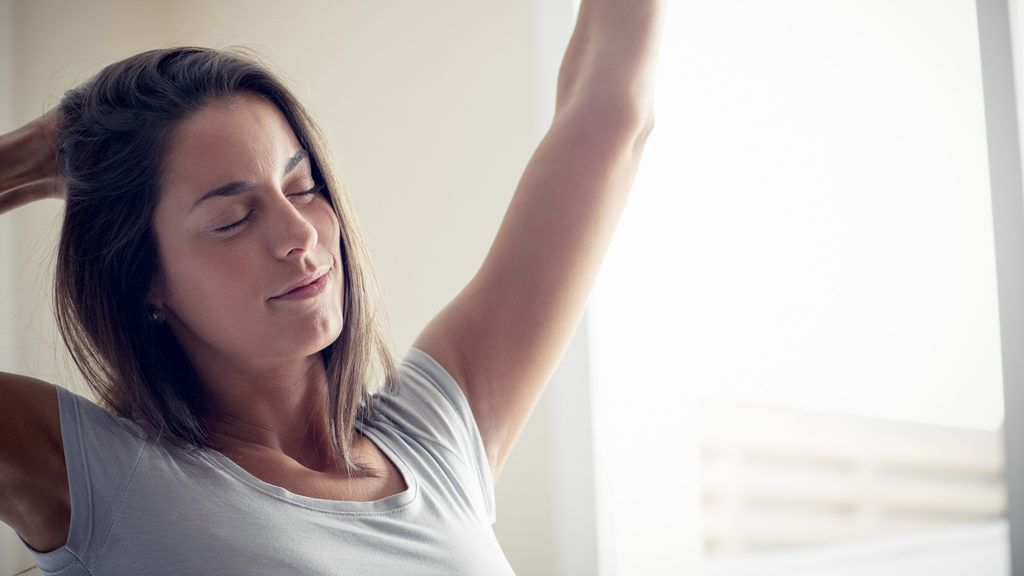 Young woman waking up in morning