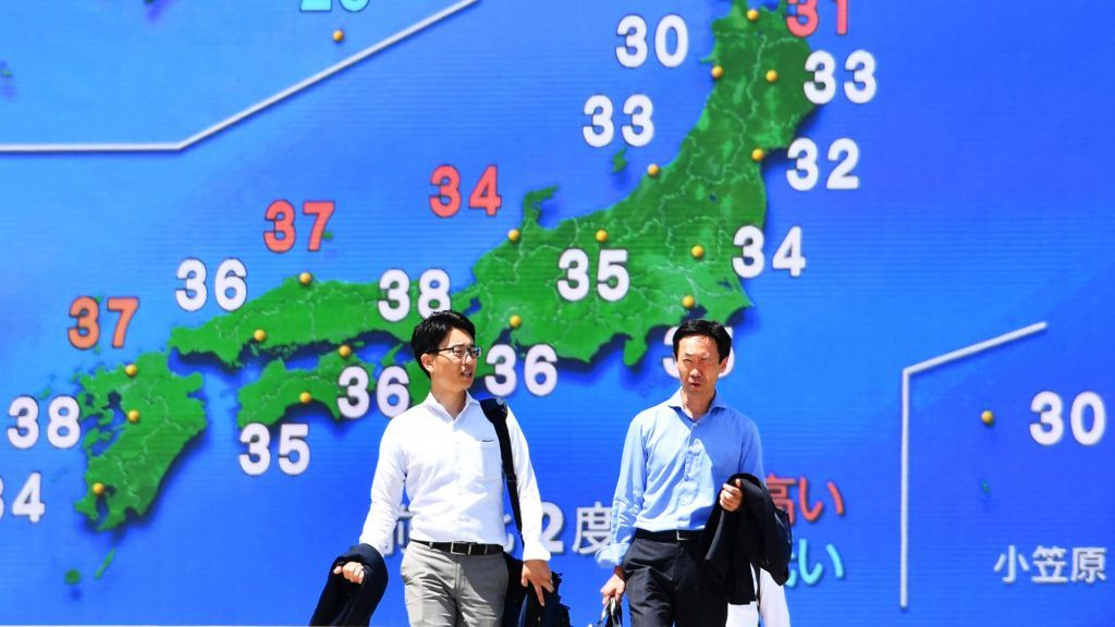 People walk in front of a TV screen broadcasting the weather forecast while the maximum temperature exceeds 33 degrees Celsius (about 92 degrees Fahrenheit) in Chiyoda Ward, Tokyo on July 20, 2018. According to Japan Metrological Agency, the maximum temperature was 33.2 degrees Celsius (about 92 degrees Fahrenheit) in Tokyo. The highest temperatures of some places in Japan exceeded 38 degrees Celsius (about 100 degrees Fahrenheit) have continued, and around 10 people have died recently due to heatstroke.  ( The Yomiuri Shimbun )