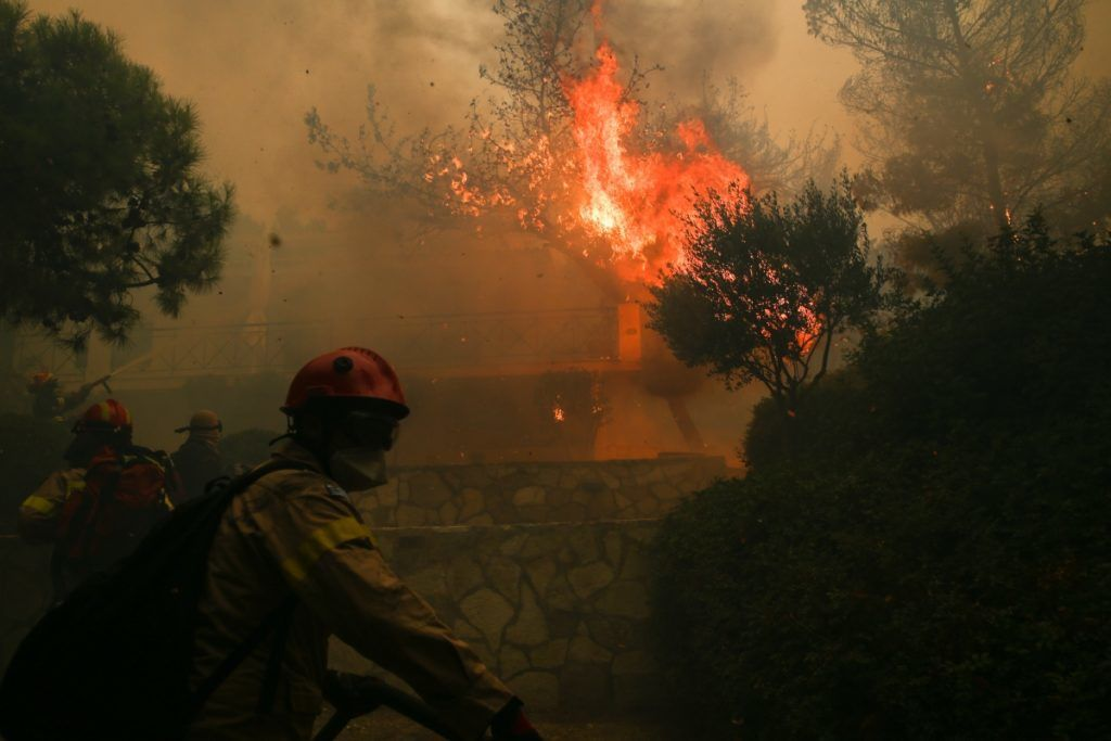 Firefighters try to extinguish a fire outside a house during a wildfire in the Gerania Mountains, in the region of Kineta, West Attica, about 50 km west of Athens, Greece on July 23, 2018. George Vitsaras / SOOC