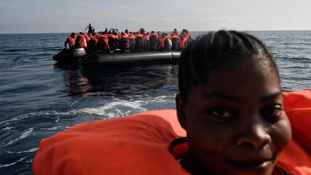 A migrant woman smiles during a rescue operation off Libya coast on May 12, 2018. 73 migrants of various nationalities, including women and children were rescued by MV Aquarius, a rescue vessel chartered by SOS-Mediterranee and Doctors Without Borders (MSF). / AFP PHOTO / LOUISA GOULIAMAKI