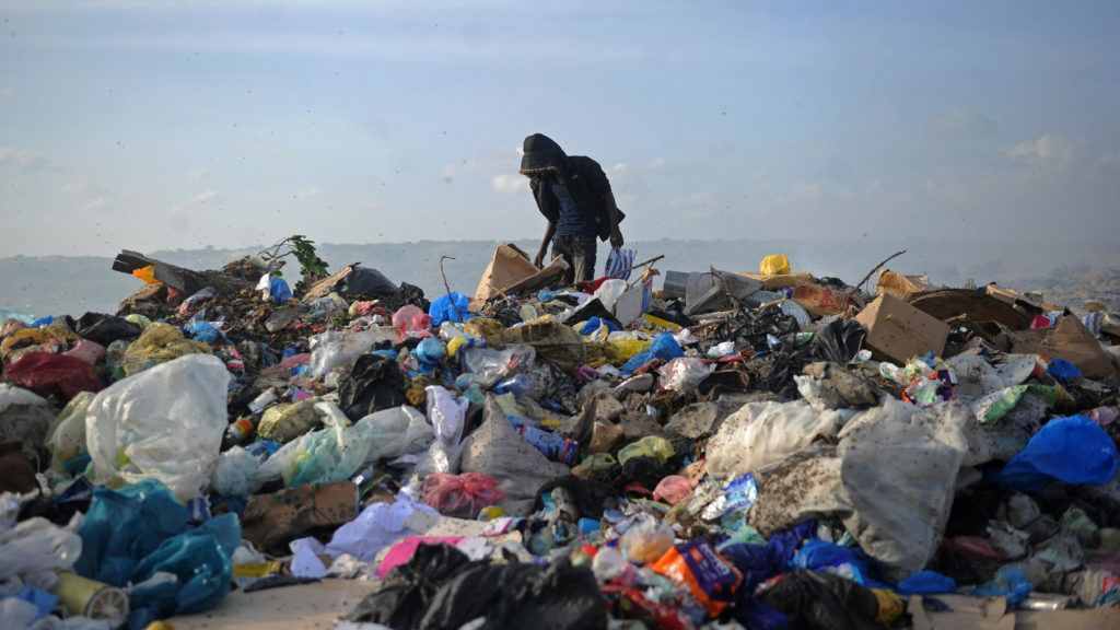 """A picture taken on June 2, 2018, shows people scavenging at the Wadajir municipal dumping site in Mogadishu, Somalia.   The United Nations celebrate on June 5 the World Environmental Day dedicated this year to the theme """"Beat Plastic Pollution"""". / AFP PHOTO / Mohamed ABDIWAHAB"""