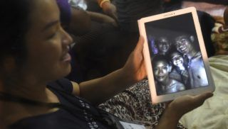 """A family member shows a picture believed to have been taken in 2017 of four of the 12 missing boys after hearing the news the group was found, near the Tham Luang cave at the Khun Nam Nang Non Forest Park in the Mae Sai district on July 2, 2018. Twelve boys and their football coach trapped in a flooded Thai cave for nine days were """"found safe"""" on late July 2, in a miracle rescue after days of painstaking searching by divers. / AFP PHOTO / LILLIAN SUWANRUMPHA / """"The erroneous mention[s] appearing in the metadata of this photo by LILLIAN SUWANRUMPHA has been modified in AFP systems in the following manner: [clarifying the caption details that the photo was taken at a previous time]. Please immediately remove the erroneous mention[s] from all your online services and delete it (them) from your servers. If you have been authorized by AFP to distribute it (them) to third parties, please ensure that the same actions are carried out by them. Failure to promptly comply with these instructions will entail liability on your part for any continued or post notification usage. Therefore we thank you very much for all your attention and prompt action. We are sorry for the inconvenience this notification may cause and remain at your disposal for any further information you may require."""""""