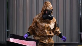 An investigator wearing a camouflaged protective suit, gloves and a gas mask works in Rollestone Street outside the John Baker House Sanctuary Supported Living in Amesbury, southern England, on July 6, 2018 in connection with the investigation after a man and woman were found unconscious in circumstances that sparked a major incident after presumed contact with what was later identified as the nerve agent Novichok. Police on July 6, 2018, raced to find the object that contaminated a British couple with the Soviet-made Novichok nerve agent in southwestern England where a former Russian spy was poisoned with the same toxin four months ago. / AFP PHOTO / Chris J Ratcliffe