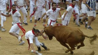 A reveller is tossed by a heifer bull during festivities in the bullring on the first day of the San Fermin bull run festival in Pamplona, northern Spain, on July 7, 2018. Each day at 8am hundreds of people race with six bulls, charging along a winding, 848.6-metre (more than half a mile) course through narrow streets to the city's bull ring, where the animals are killed in a bullfight or corrida, during this festival dating back to medieval times and also featuring religious processions, folk dancing, concerts and round-the-clock drinking.      / AFP PHOTO / JOSE JORDAN
