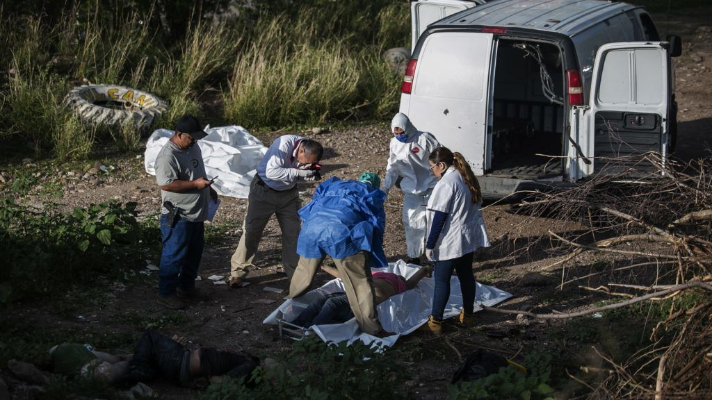 EDITORS NOTE: Graphic content / Forensic personnel inspect the bodies of three people found murdered in Culiacan, Sinaloa State, Mexico, on July 11, 2018. / AFP PHOTO / RASHIDE FRIAS
