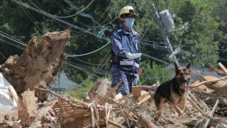 A member of Maritime Self Defense Forces searches for missing persons at a flood damage site in Kure, Hiroshima prefecture on July 12, 2018.   The toll in record rains that have devastated parts of Japan rose July 12 to 199, a top government spokesman said. Local media said search operations are continuing, with dozens of people still missing after the worst weather-related disaster in Japan in over three decades.  / AFP PHOTO / JIJI PRESS / JIJI PRESS / Japan OUT