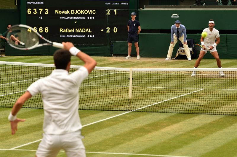 Serbia's Novak Djokovic (L) watches the all after returning to Spain's Rafael Nadal during the continuation of their men's singles semi-final match on the twelfth day of the 2018 Wimbledon Championships at The All England Lawn Tennis Club in Wimbledon, southwest London, on July 14, 2018. / AFP PHOTO / Glyn KIRK / RESTRICTED TO EDITORIAL USE