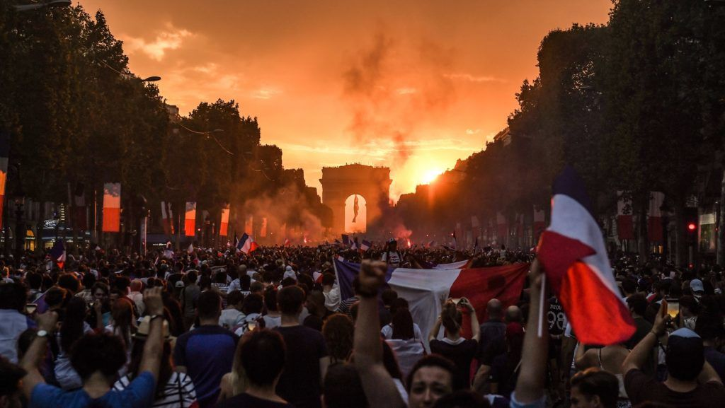 People celebrate France's victory in the Russia 2018 World Cup final football match between France and Croatia, on the Champs-Elysees avenue in Paris on July 15, 2018.  / AFP PHOTO / Eric FEFERBERG