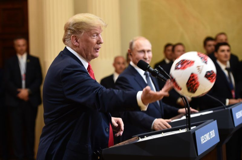 """US President Donald Trump (L) throws a soccer ball to his wife after receiving it by Russia's President Vladimir Putin during a joint press conference after a meeting at the Presidential Palace in Helsinki, on July 16, 2018. The US and Russian leaders opened an historic summit in Helsinki, with Donald Trump promising an """"extraordinary relationship"""" and Vladimir Putin saying it was high time to thrash out disputes around the world.  / AFP PHOTO / Brendan SMIALOWSKI"""