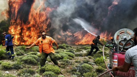 """Firefighters and volunteers try to extinguish flames during a wildfire at the village of Kineta, near Athens, on July 24, 2018.  Raging wildfires killed 74 people including small children in Greece, devouring homes and forests as terrified residents fled to the sea to escape the flames, authorities said Tuesday. / AFP PHOTO / Valerie GACHE / """"The erroneous mention[s] appearing in the metadata of this photo by ANGELOS TZORTZINIS has been modified in AFP systems in the following manner: [-VALERIE GACHE--] instead of [--ANGELOS TZORTZINIS -]. Please immediately remove the erroneous mention[s] from all your online services and delete it (them) from your servers. If you have been authorized by AFP to distribute it (them) to third parties, please ensure that the same actions are carried out by them. Failure to promptly comply with these instructions will entail liability on your part for any continued or post notification usage. Therefore we thank you very much for all your attention and prompt action. We are sorry for the inconvenience this notification may cause and remain at your disposal for any further information you may require."""""""