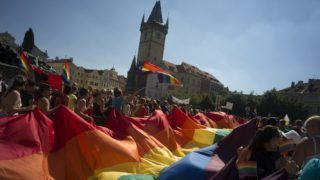 People hold up a large rainbow flag as they march across the Old Town Square during the third gay pride festival in the Czech capital Prague on August 17, 2013.    AFP PHOTO / MICHAL CIZEK / AFP PHOTO / MICHAL CIZEK