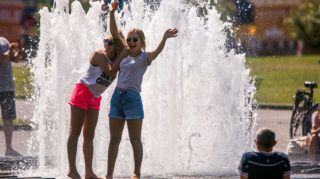 31 July 2018, Berlin, Germany: Tourists from Spain cool off at the fountain in the Lustgarten. The last day in July could be the warmest day of the month or even the year. Peak temperatures are expected in central and eastern Germany. Photo: Jens Büttner/dpa-Zentralbild/dpa