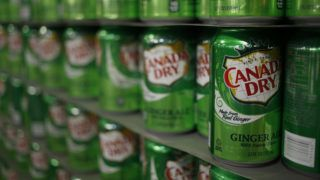Empty cans of Canada Dry Ginger Ale sit stacked in a warehouse before being filled at the Dr. Pepper Snapple Group Inc. bottling plant in Louisville, Kentucky, U.S., on Tuesday, April 21, 2015. Dr. Pepper Snapple Group Inc., producers of 7up and A&W Root Beer, is scheduled to release earnings figures on April 23. Photographer: Luke Sharrett/Bloomberg via Getty Images