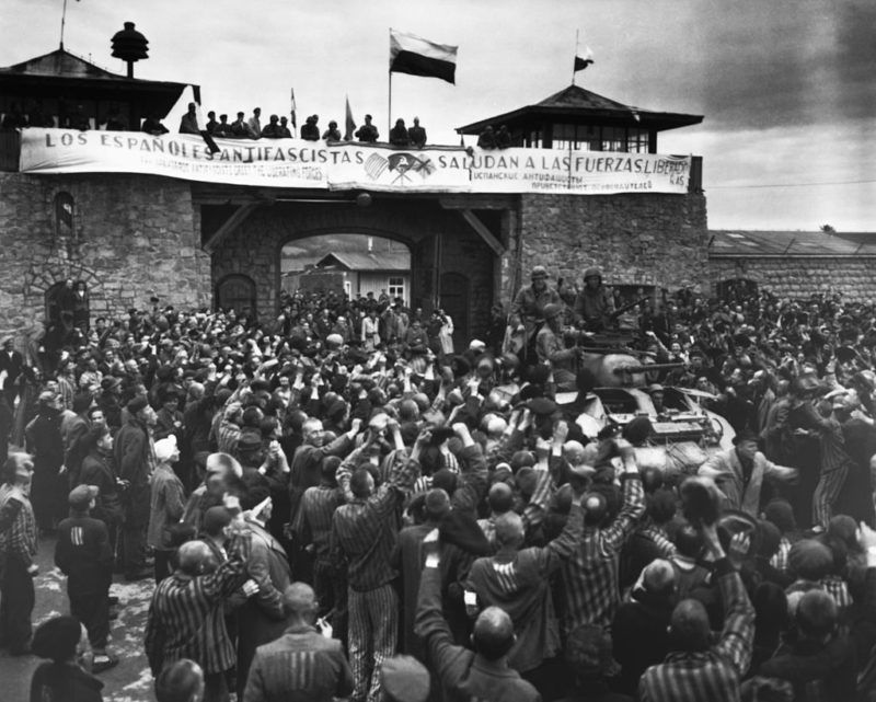 Liberated prisoners in the Mauthausen concentration camp near Linz, Austria, give rousing welcome to Cavalrymen of the 11th Armored Division. The anti-fascist banner across the wall was made by Spanish Loyalist prisoners. May 6, 1945. | Location: near Linz, Austria. (Photo by © CORBIS/Corbis via Getty Images)