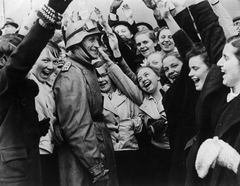 14th March 1938:  Ecstatic crowds in Salzburg cheer and salute German troops as they enter the city during the Anschluss.  (Photo by Central Press/Getty Images)
