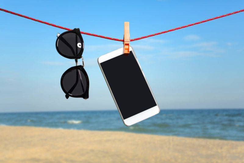 Sunglasses and mobile phone on summer vacation background