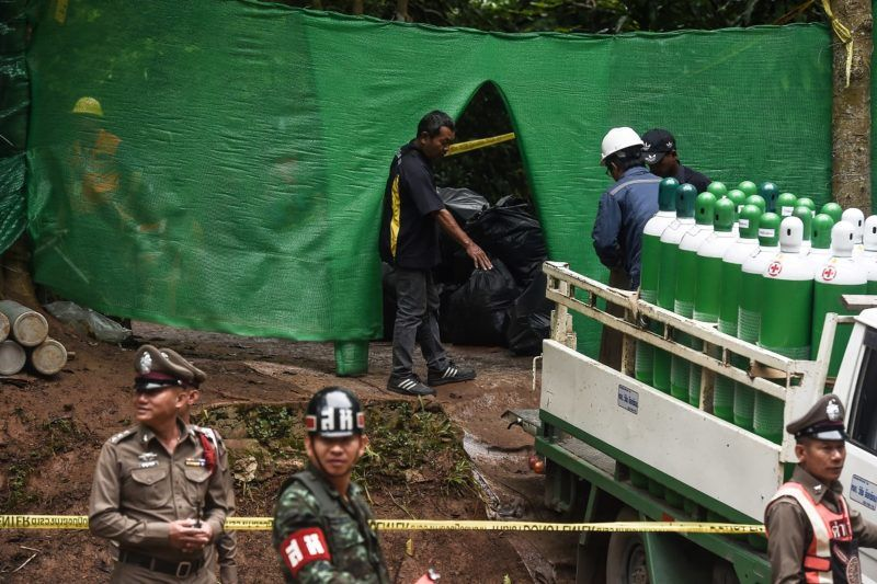 """Rescue workers move air tanks at the Tham Luang cave area as operations continue for the 12 boys and their coach trapped at the cave in Khun Nam Nang Non Forest Park in the Mae Sai district of Chiang Rai province on July 8, 2018. Thai authorities told media on July 8 to leave a camp site near the cave where 12 boys and their coach have been trapped for more than two weeks so that """"victims"""" could be helped, possibly signalling a long-awaited rescue effort to get them out. / AFP PHOTO / LILLIAN SUWANRUMPHA"""