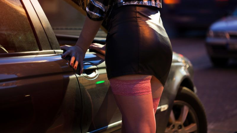 Woman in leather mini skirt standing next to car