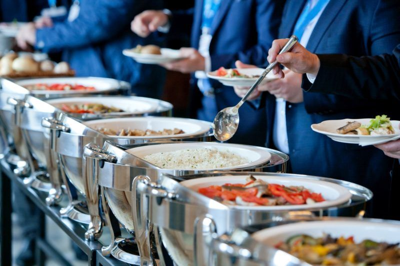 men in blue suits choosing food at a banquet