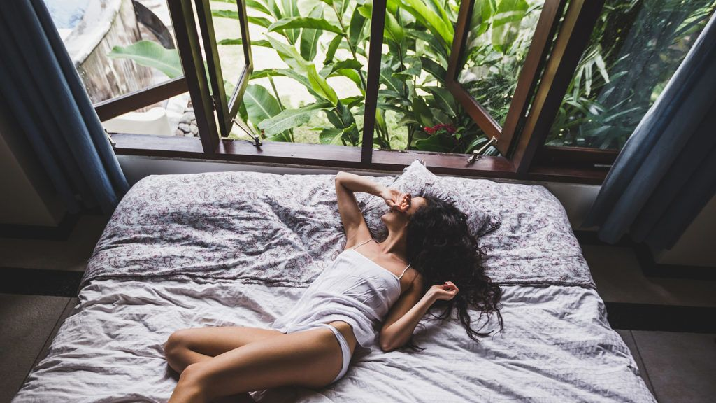 Woman waking up in bed in the morning, view from window on tropical garden. Lifestyle photo
