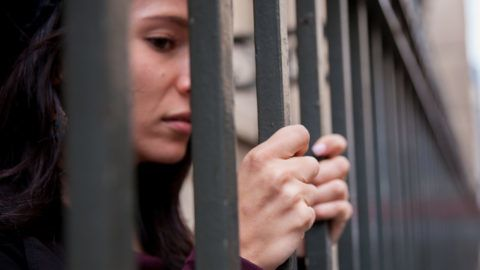 Close up of a female prisoner behind bars. Stress and anxiety showing on her face. Focus on her hands.