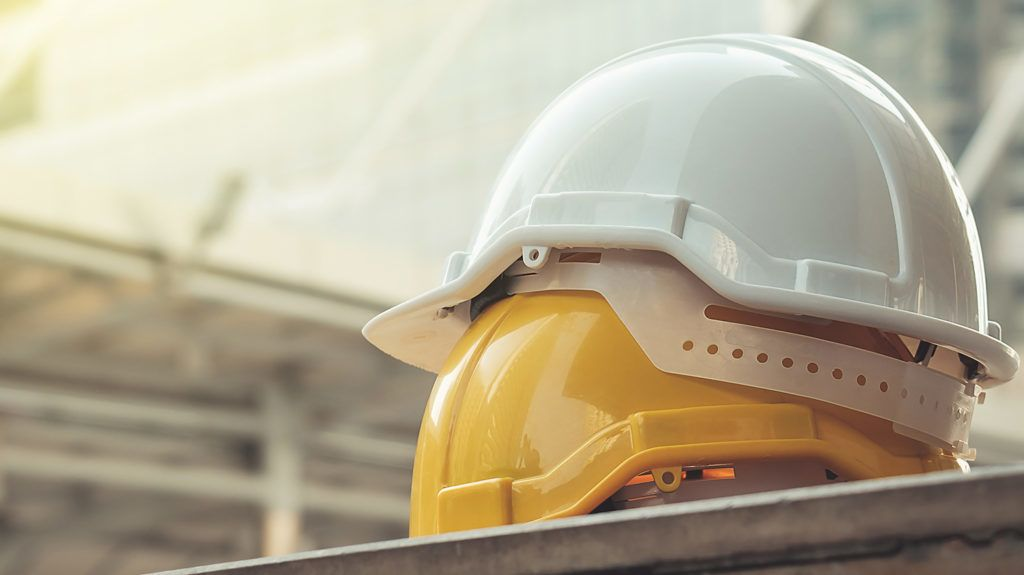 white, yellow hard safety helmet hat for safety project of workman as engineer or worker, on concrete floor on city