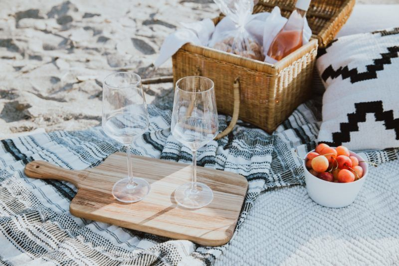 A photo of a styled beach picnic with wine glasses, picnic basket and blankets.