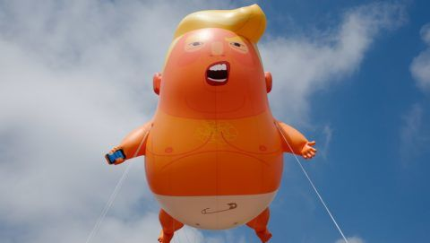 """A giant balloon inflated by activists depicting US President Donald Trump as an orange baby is seen during a demonstration against Trump's visit to the UK in Parliament Square in London on July 13, 2018. US President Donald Trump launched an extraordinary attack on Prime Minister Theresa May's Brexit strategy, plunging the transatlantic """"special relationship"""" to a new low as they prepared to meet Friday on the second day of his tumultuous trip to Britain. / AFP PHOTO / Tolga AKMEN"""
