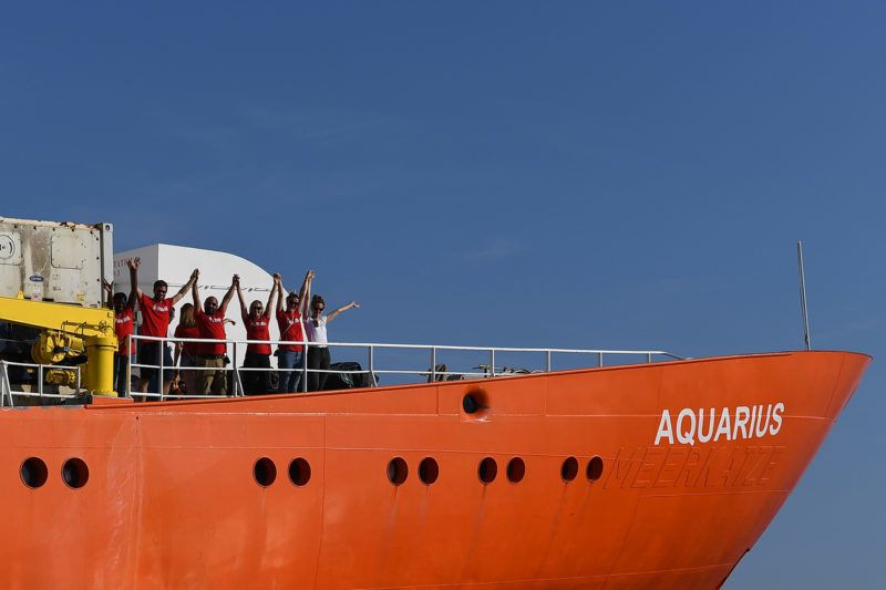 Crew members wave as the rescue ship Aquarius, chartered by French aid group SOS Mediterranee and Doctors Without Borders (MSF), leaves the harbour of Marseille, southeastern France, on August 1, 2018, after having been docked for a month for maintenance work. The French NGO operating the rescue ship Aquarius, which precipitated a European political crisis in June after both Italy and Malta blocked it from docking with 630 migrants aboard, said on August 1 that nothing would stop it from rescuing migrants from the Mediterranean as its ship prepared to resume its mission off the Libyan coast. / AFP PHOTO / BORIS HORVAT