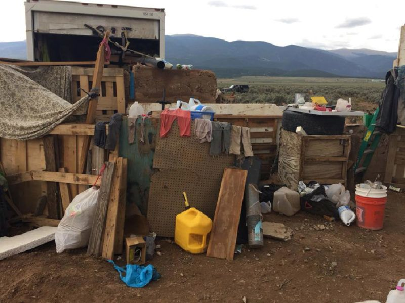 """This handout photo released by the Taos County Sheriff's Office on August 4, 2018 shows a view of a makeshift compound in Amalia, New Mexico, where police rescued 11 children and arrested two armed """"extremists.""""  Police say 11 children ages one to 15 were rescued in the US state of New Mexico after officers raided on August 3 a makeshift compound occupied by armed """"extremists."""" Two men were arrested after police found them and the children in what one officer called """"the saddest living conditions and poverty I have seen,"""" as part of the operation connected to a months-long search for an abducted three-year-old, according to New Mexico's Taos County sheriff's office. / AFP PHOTO / TAOS COUNTY SHERIFF'S OFFICE / Handout / RESTRICTED TO EDITORIAL USE - MANDATORY CREDIT """"AFP PHOTO / TAOS COUNTY SHERIFF'S OFFICE """" - NO MARKETING NO ADVERTISING CAMPAIGNS - DISTRIBUTED AS A SERVICE TO CLIENTS"""