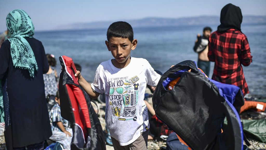 A boy is pictured as migrants from Afghanistan arrive after crossing the Aegean Sea from Turkey with a dinghy on the Greek Mediterranean island of Lesbos on August 6, 2018.More than 1,500 refugees and migrants have died trying to cross the Mediterranean Sea to Europe in the first seven months of this year, over half of them in June and July, the UN refugee agency said on August 3, 2018. / AFP PHOTO / Aris MESSINIS