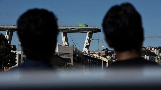Two men look at the Morandi motorway bridge one day after a section collapsed in Genoa on August 15, 2018.Nearly 40 people died on August 14, 2018 when a giant motorway bridge collapsed in Genoa in northwestern Italy, with the death toll expected to mount further. / AFP PHOTO / Piero CRUCIATTI